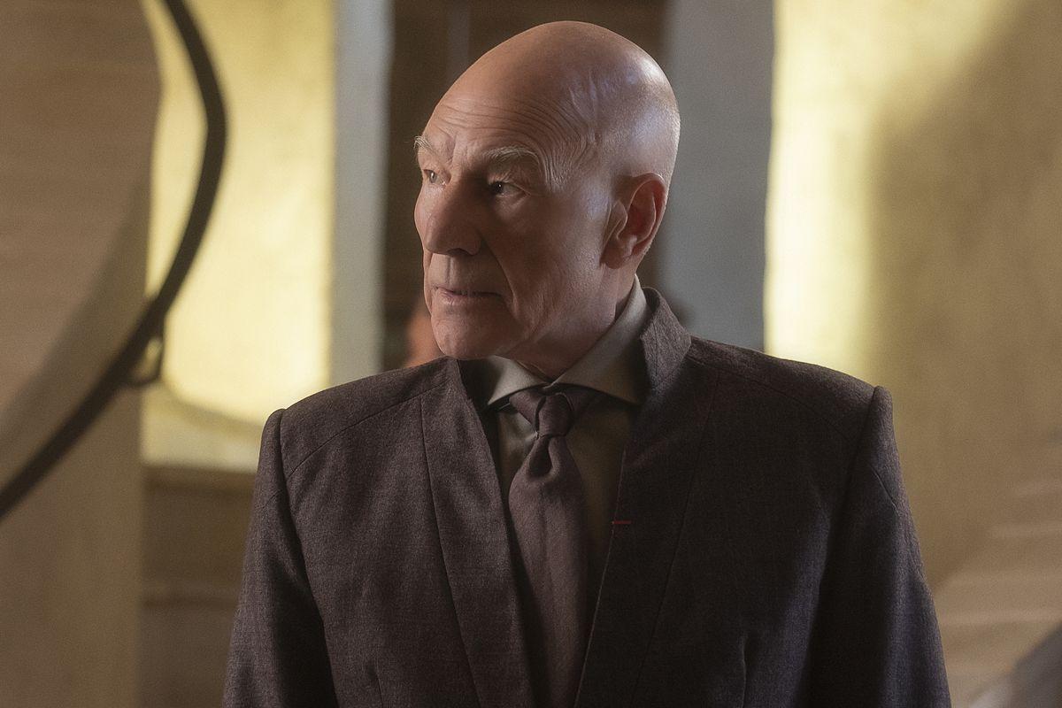Patrick Stewart as Star Trek's Jean-Luc Picard wears a brown civilian suit and brown tie.