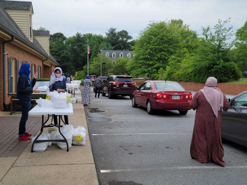 Cars line up alongside tables laden with plastic bags of takeout containers. A few women pass the bags through car windows.