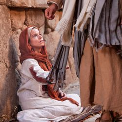 A woman with an issue of blood touches the clothes of Jesus in a Bible Video.