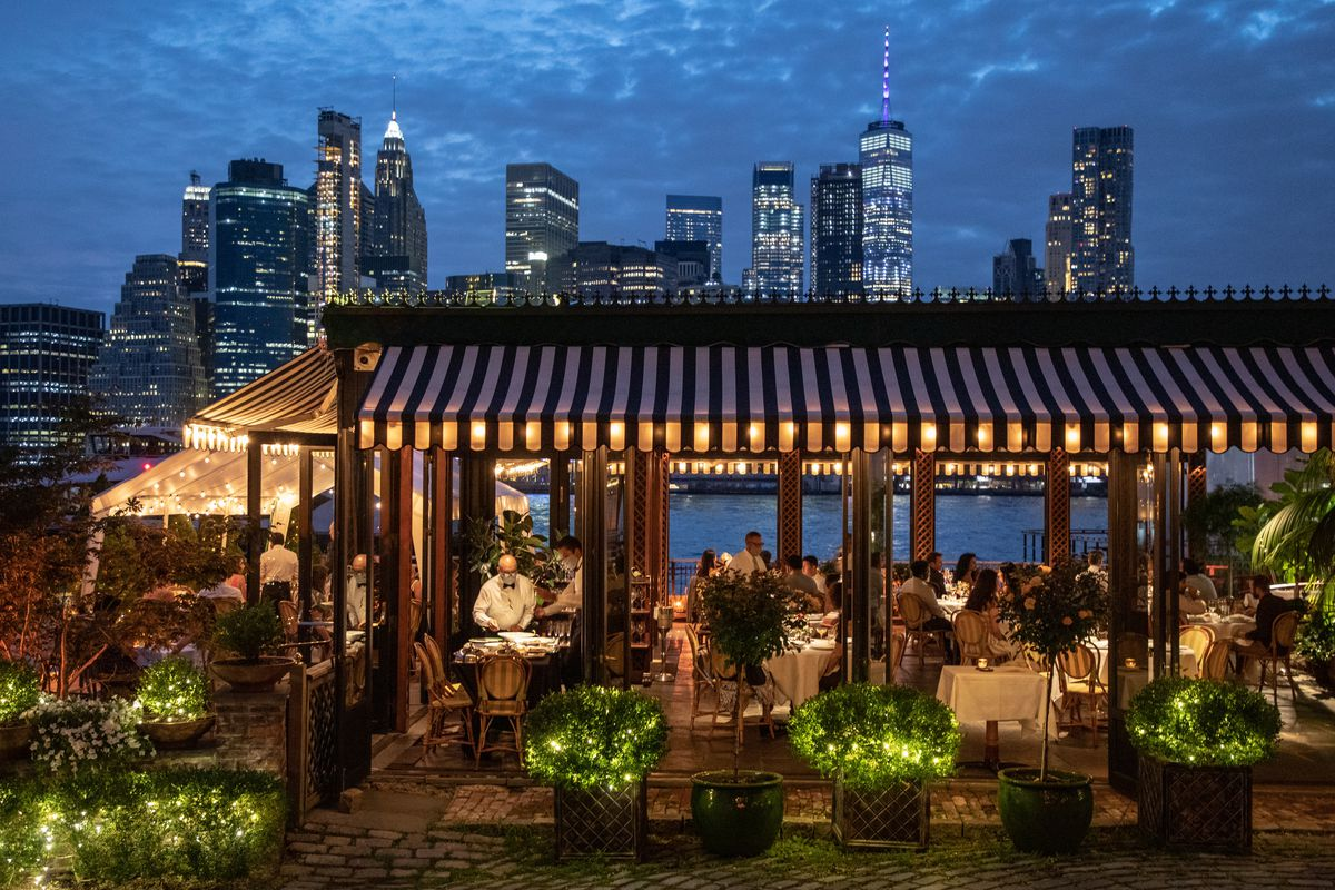Wide photo of The River Cafe during service with the New York City skyline in the background.