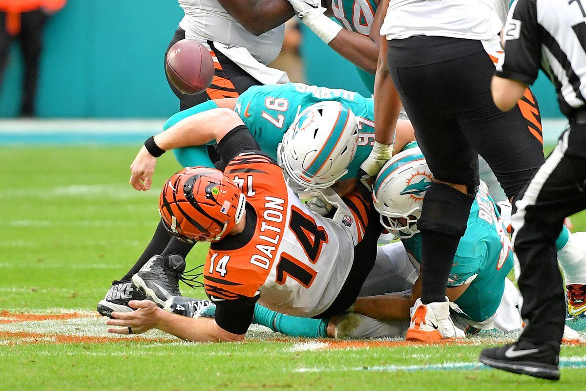 Cincinnati Bengals quarterback Andy Dalton fumbles the ball as Miami Dolphins defensive end Trent Harris makes the hit during the second half at Hard Rock Stadium.