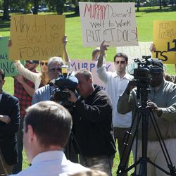 Democratic candidate for U.S. Senate Chris Murphy, front left, speaks to an audience at a news conference as supporters for opponent Linda McMahon hold up signs in Hartford, Conn., Tuesday, Sept. 25, 2012.  Murphy says he's seeking to refocus Connecticut's increasingly personal and contentious Senate race, challenging his Republican rival Linda McMahon to talk about issues that the voters care about.