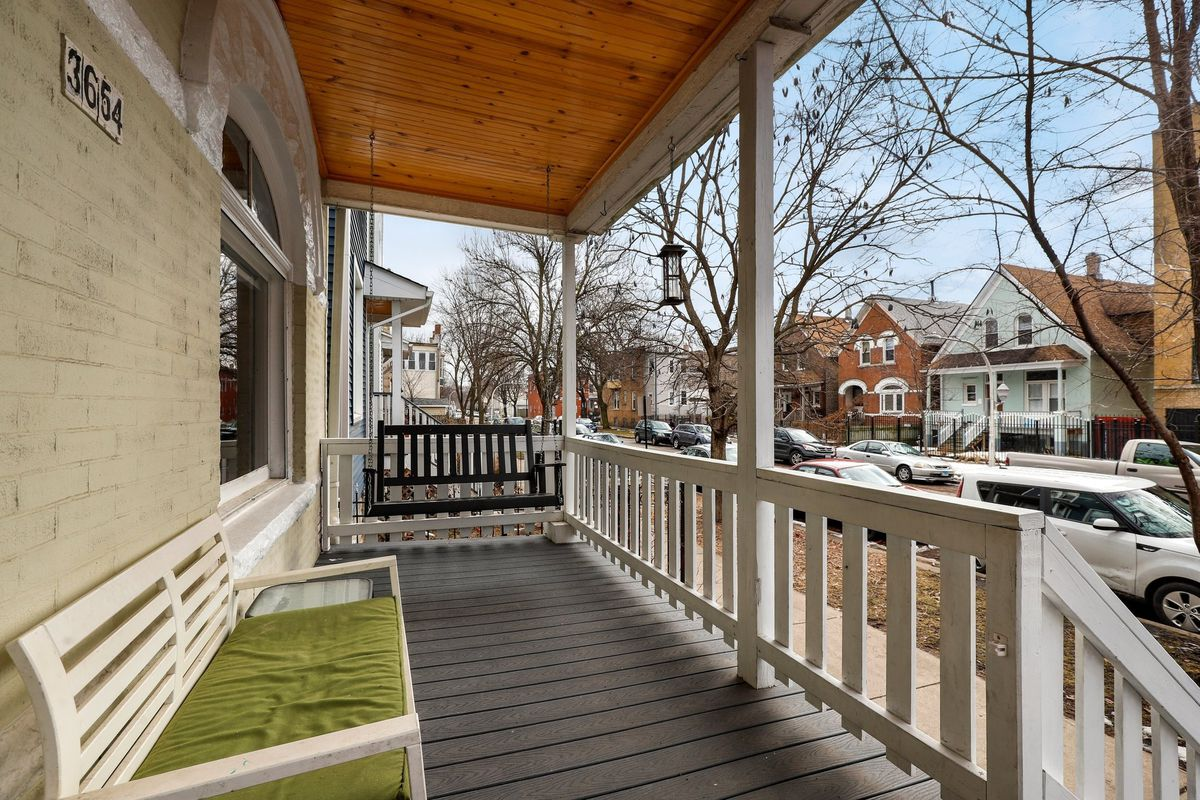 A front porch with a swinging bench and an arched window.