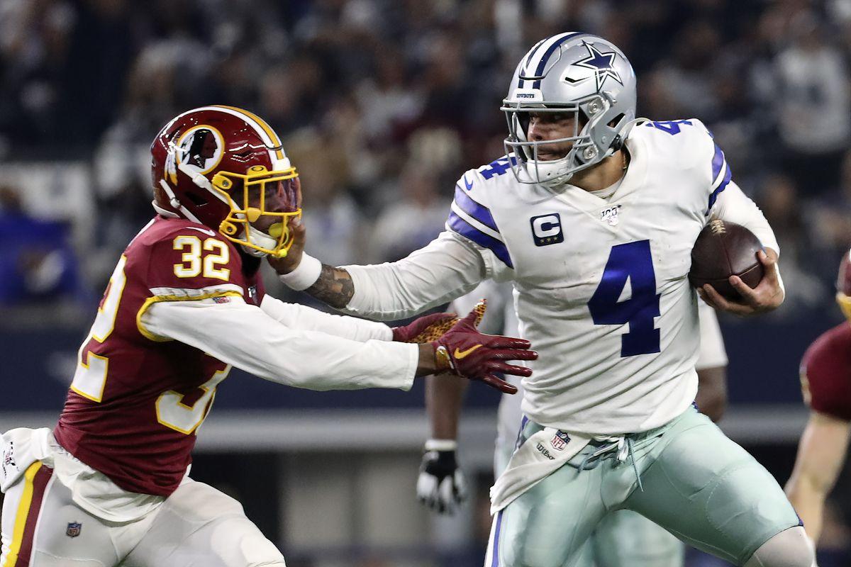 Dallas Cowboys quarterback Dak Prescott stiff arms Washington Redskins cornerback Jimmy Moreland during the second half at AT&T Stadium.