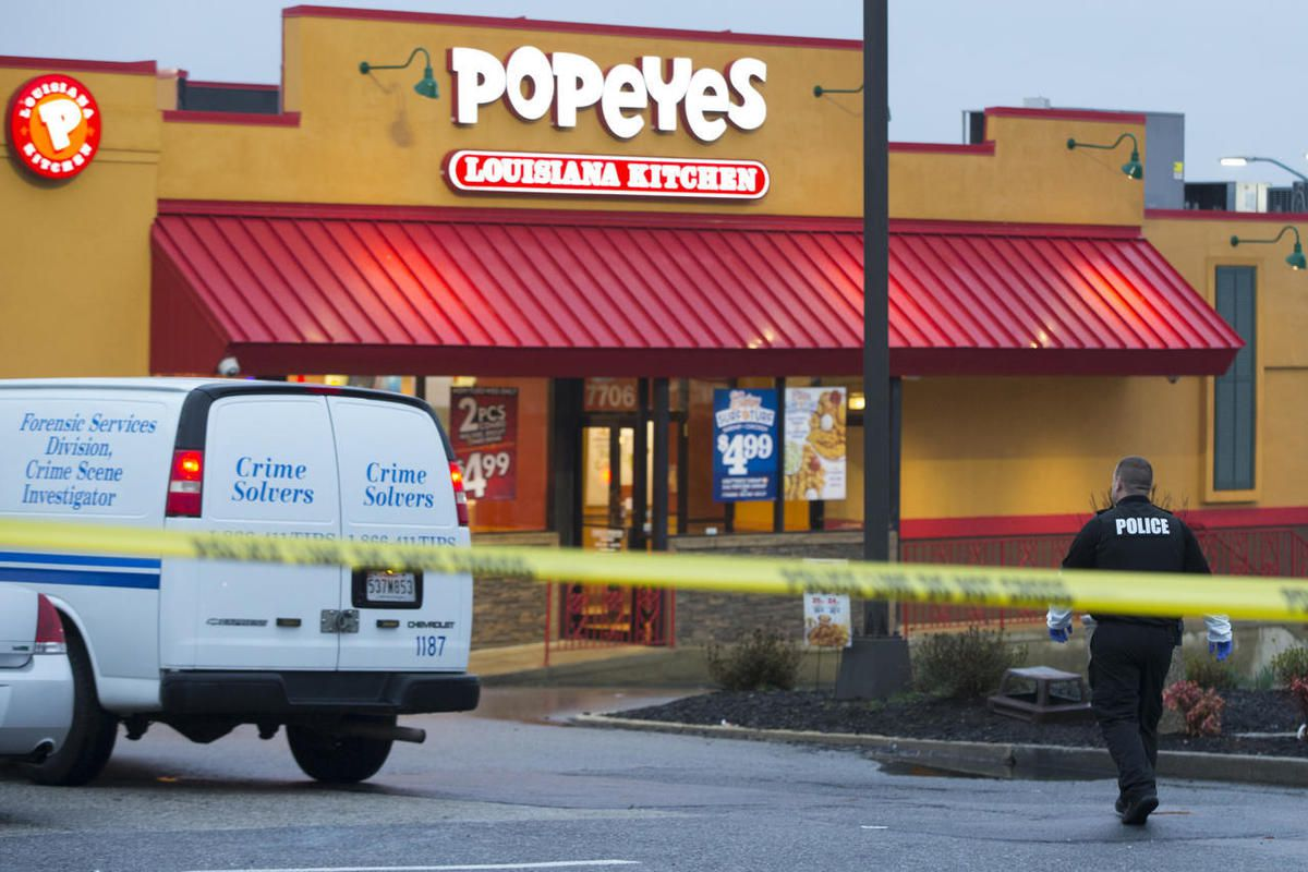 A police officer walks outside a Popeyes restaurant during an investigation into the shooting of a Prince George's County police officer outside a police station, on Sunday, March 13, 2016, in Hyattsville, Md.