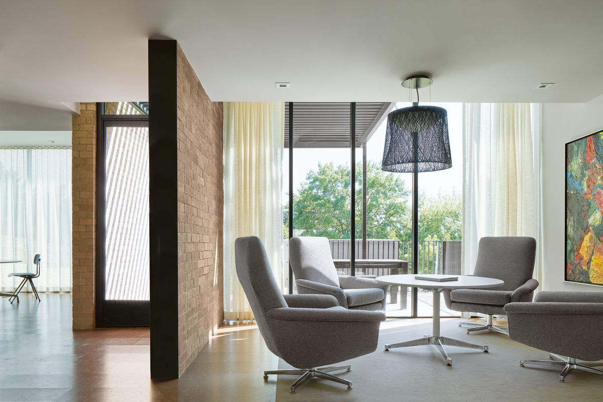 Photo of a midcentury office building interior with a brick wall extending partially inside, a steel door with a glass inset to the left, and a wall of floor-to-ceiling windows to the right. Four modern armchairs are arranged around a round modern table on the right.