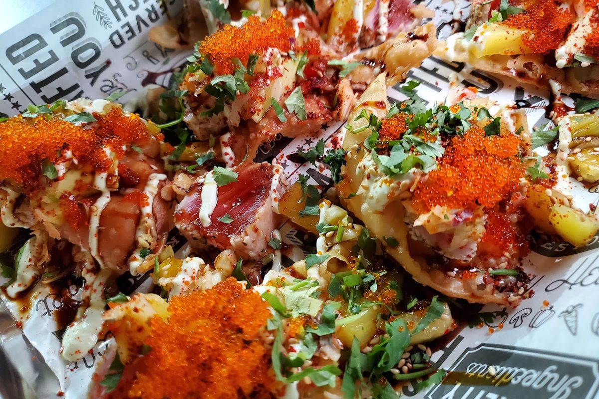 ahi tuna with pineapple and fish roe are seen on wanton chips