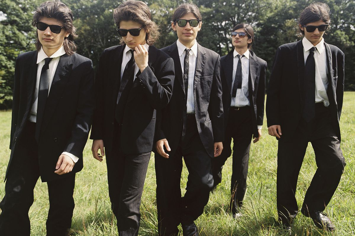 Five boys, all dressed in black suits and sunglasses, walk through a field.