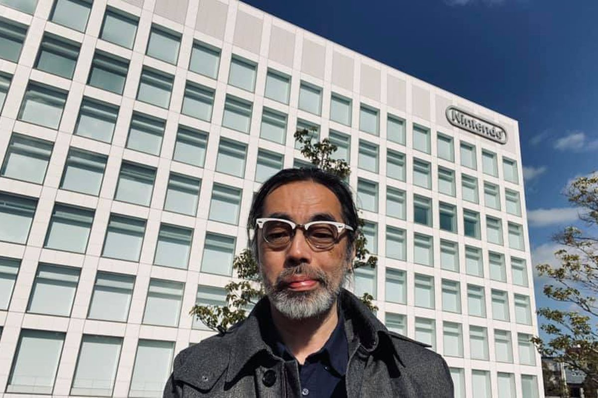 a man with glasses standing in front of Nintendo's blocky shaped headquarters building