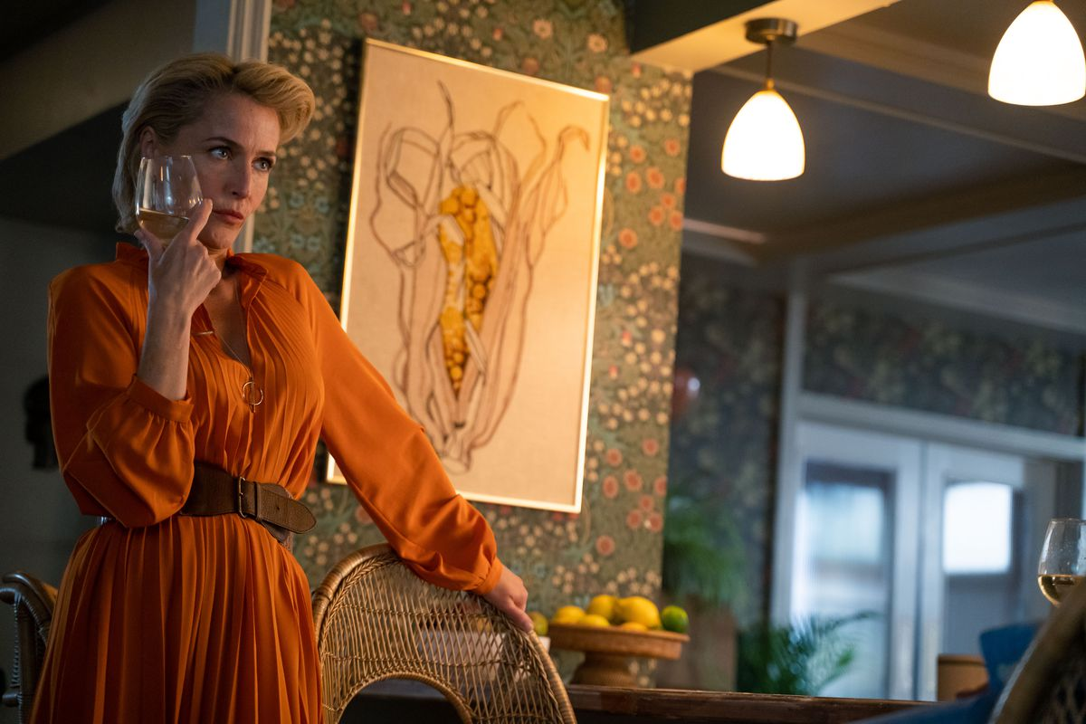 gillian anderson in sex education, she wears an orange dress and holds a wineglass