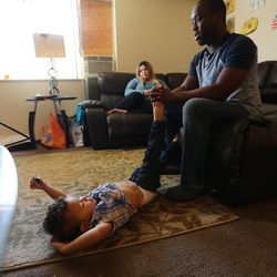 Lamar Ross, right, talks about how his family believes his uncle, Patrick Harmon, was murdered as Ross' wife, Chayse Maryie, looks on and son, Jorrick, lays on the floor of their Ogden home on Monday, Oct. 9, 2017. Harmon was shot and killed by a Salt Lake City police officer in August.