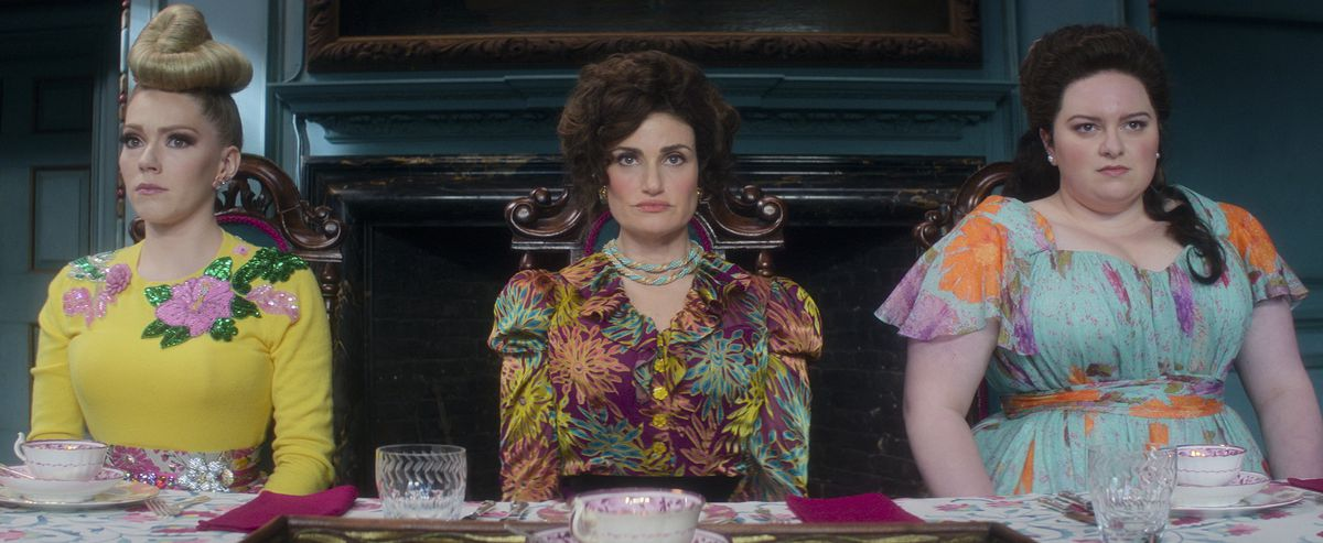 Cinderella's stepmother (Idina Menzel) and stepsisters sit in a line looking grouchy in Amazon's Cinderella