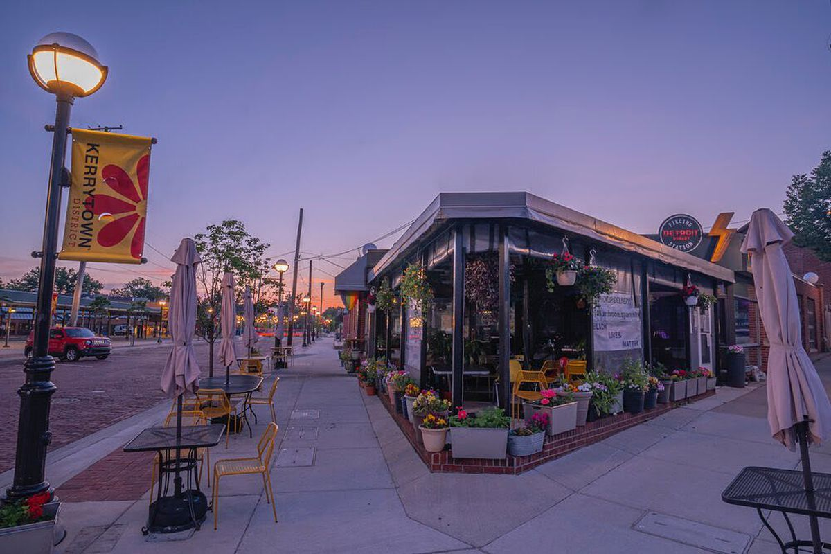 A photo of Detroit Street Filling Station from the corner looking at the restaurant and patio at twilight.
