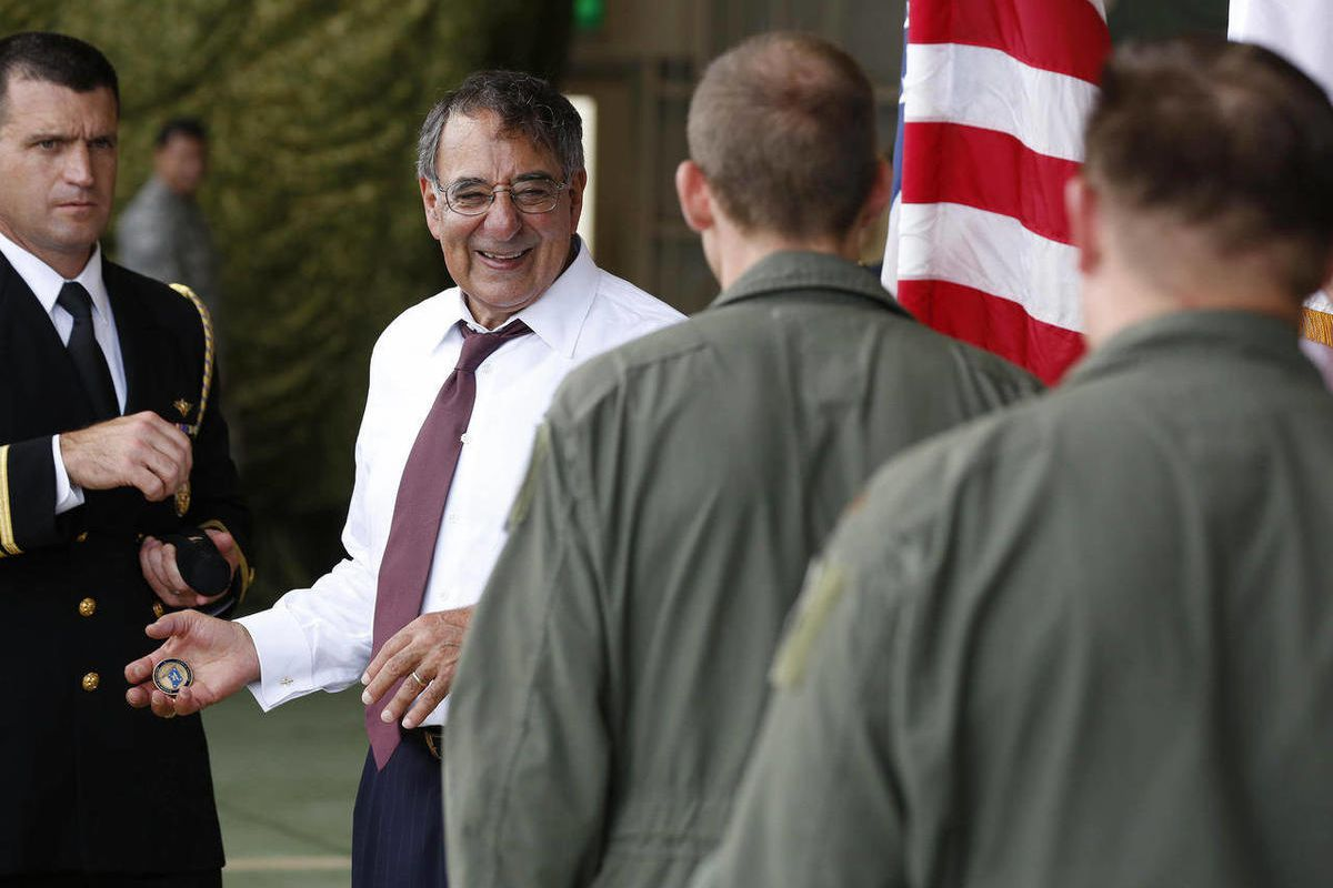 """U.S. Secretary of Defense Leon Panetta, second left, prepares to give """"Challenge Coins"""" to U.S. military personnel stationed at Yokota Air Base in Yokota, Japan, Monday, Sept. 17, 2012. Panetta, who is on the first official stop of a three nation tour to"""