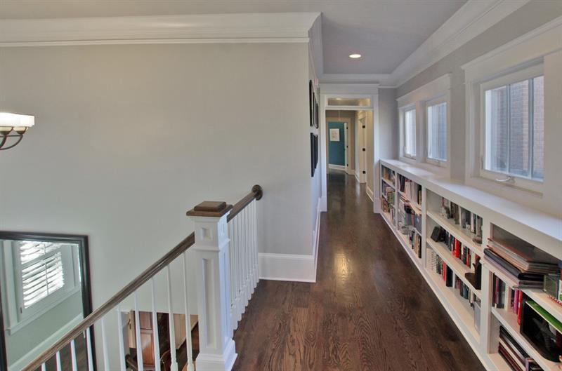 A long hallway with a long built-in bookshelf.