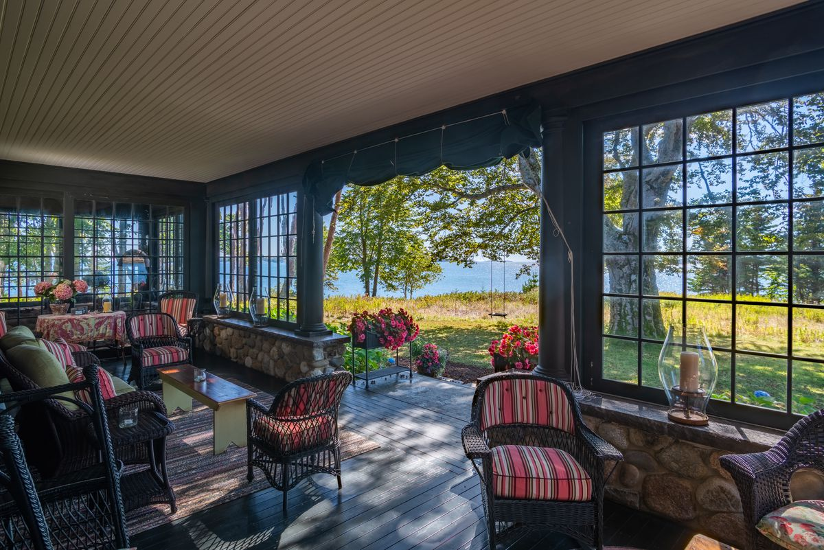 An enclosed glass porch has green trim, striped patio furniture, and views out to the water.