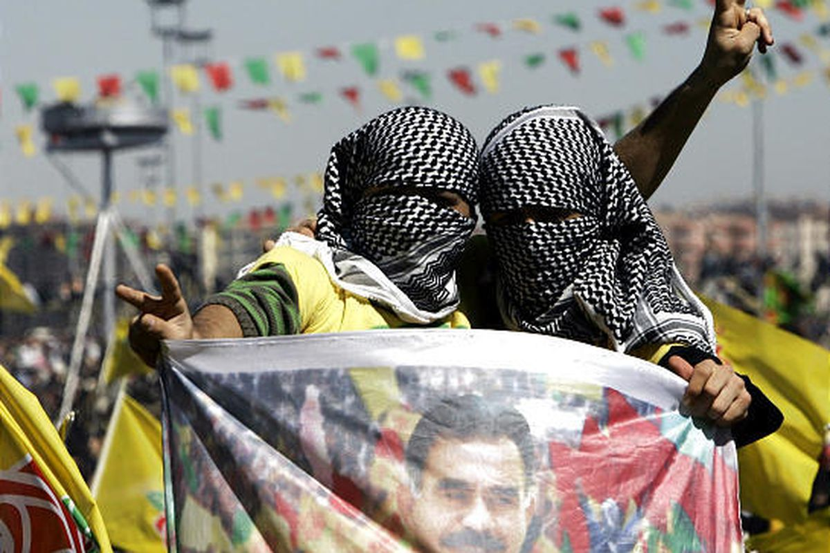 Masked supporters wave a poster of jailed Kurdish rebel leader  Abdullah Ocalan during the Nowruz celebrations in Diyarbakir, Turkey.