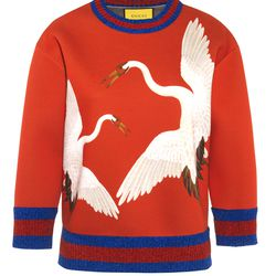Gucci re-imagined its Heron print for this electric red neoprene sweatshirt. The neckline and sleeves are made from a glittery lurex.