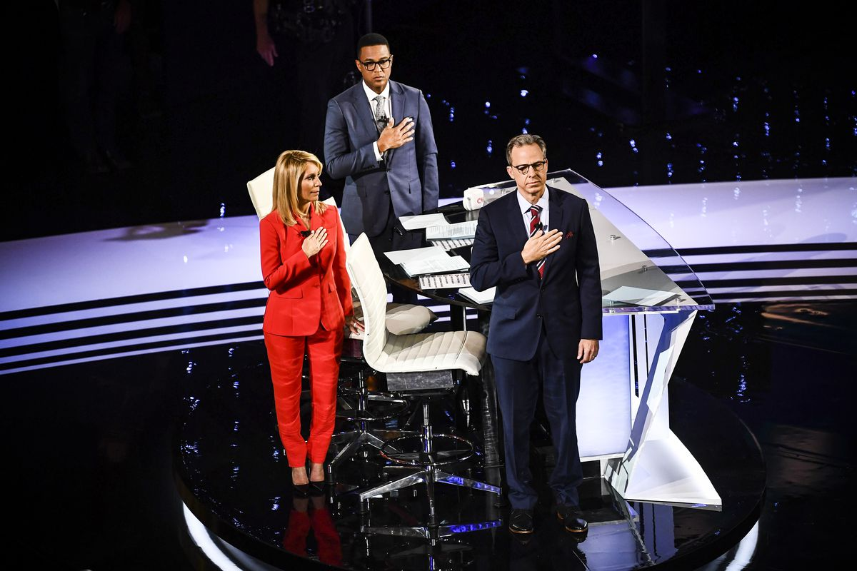 CNN moderators Don Lemon (center), Dana Bash (left) and Jake Tapper (right) stand for the national anthem ahead of the first round of the second Democratic primary debate on July 30, 2019.