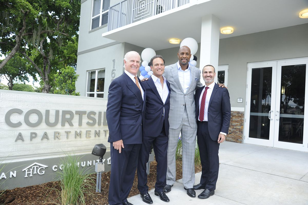 Randy Rieger, Allen Furst, Alonzo Mourning, and Matthew Rieger in front of a grey affordable housing complex in Overtown