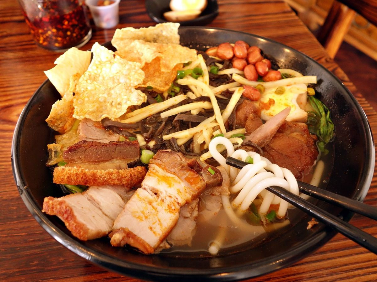 A noodle bowl filled with crispy wontons, meat, peanuts, and vegetables.