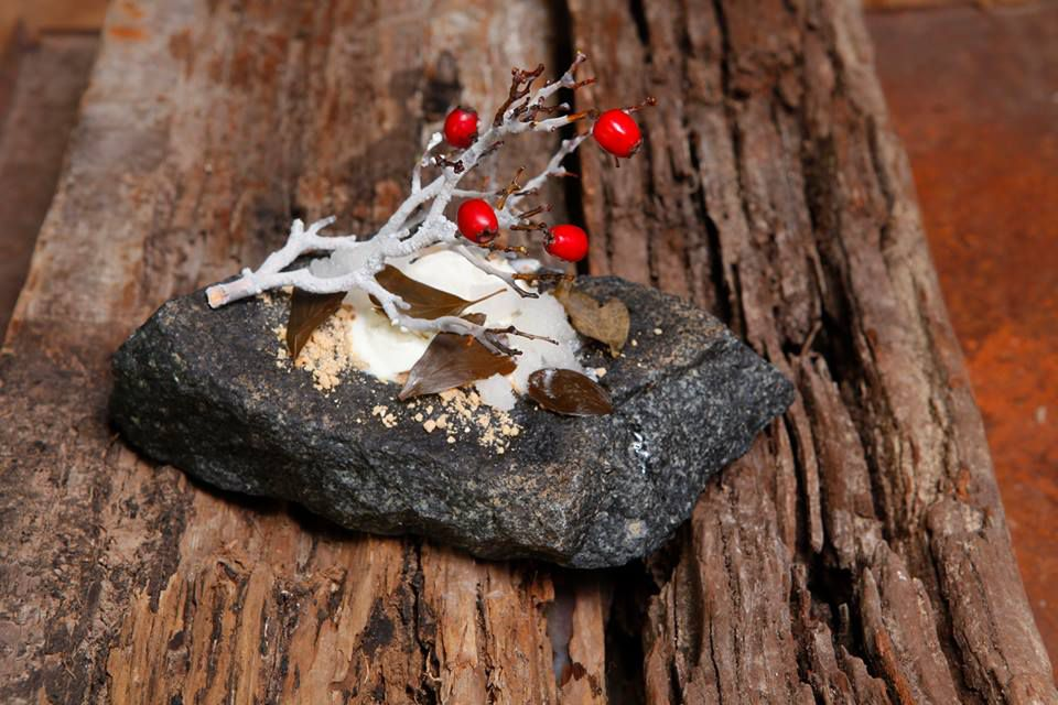 Food resembling a rock topped with a twig, a dusting of snow and leaves, and bright berries, all sitting on a coarse wooden plank