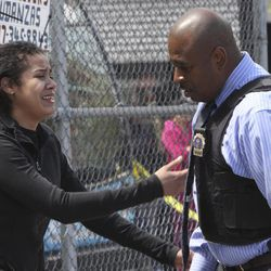 A woman, who says she is related to a man who was killed, speaks to a police officer at the crime scene in the East Harlem neighborhood of Manhattan, Thursday, April 12, 2012 in New York.  An armed bandit was killed Thursday during a chaotic getaway following a robbery at an East Harlem pharmacy of prescription painkillers and cash, police said.