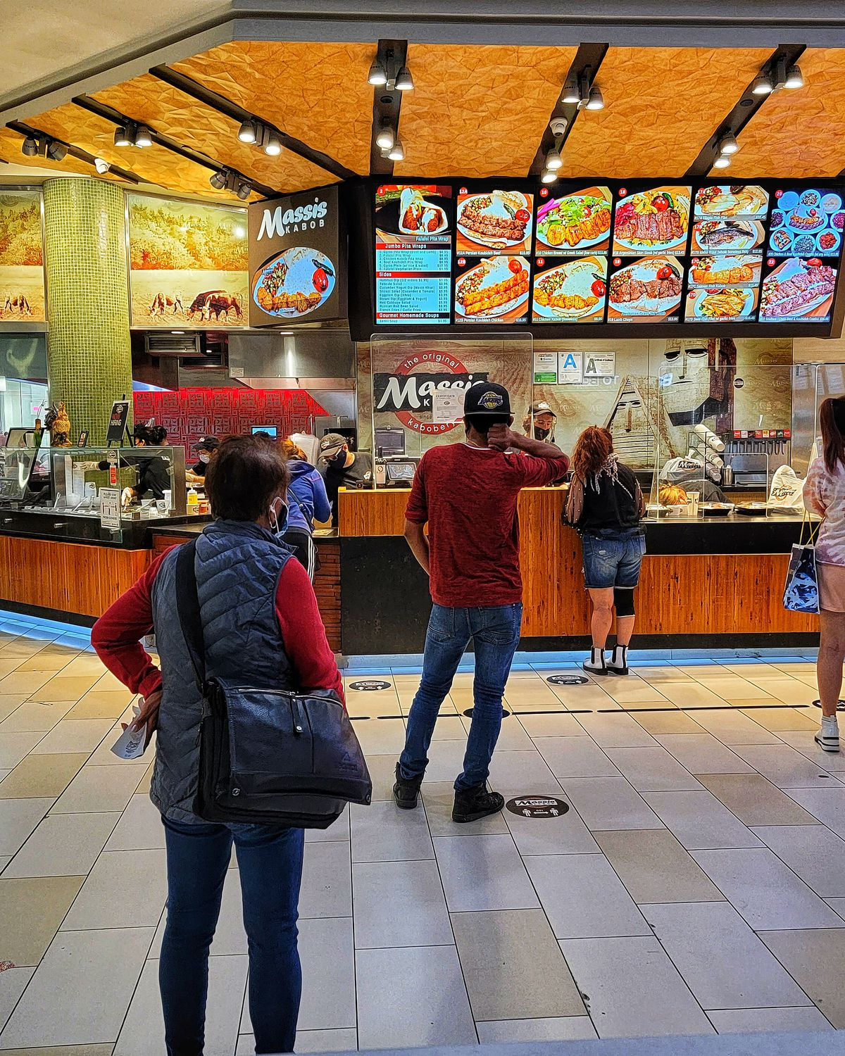 Customers wait for falafel and shawarma and skewers from a popular food court stand in a mall.