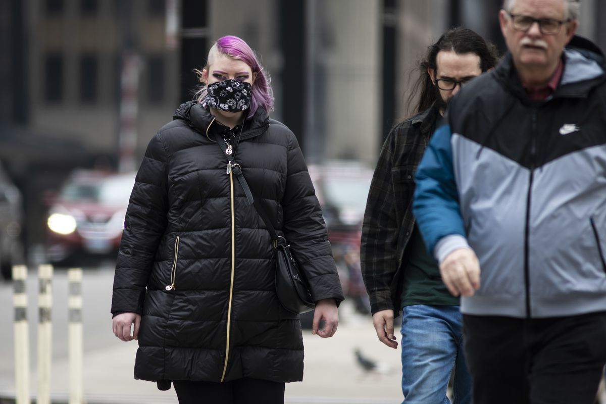 A woman in the Loop wears a face mask Thursday amid growing fear about the coronavirus.