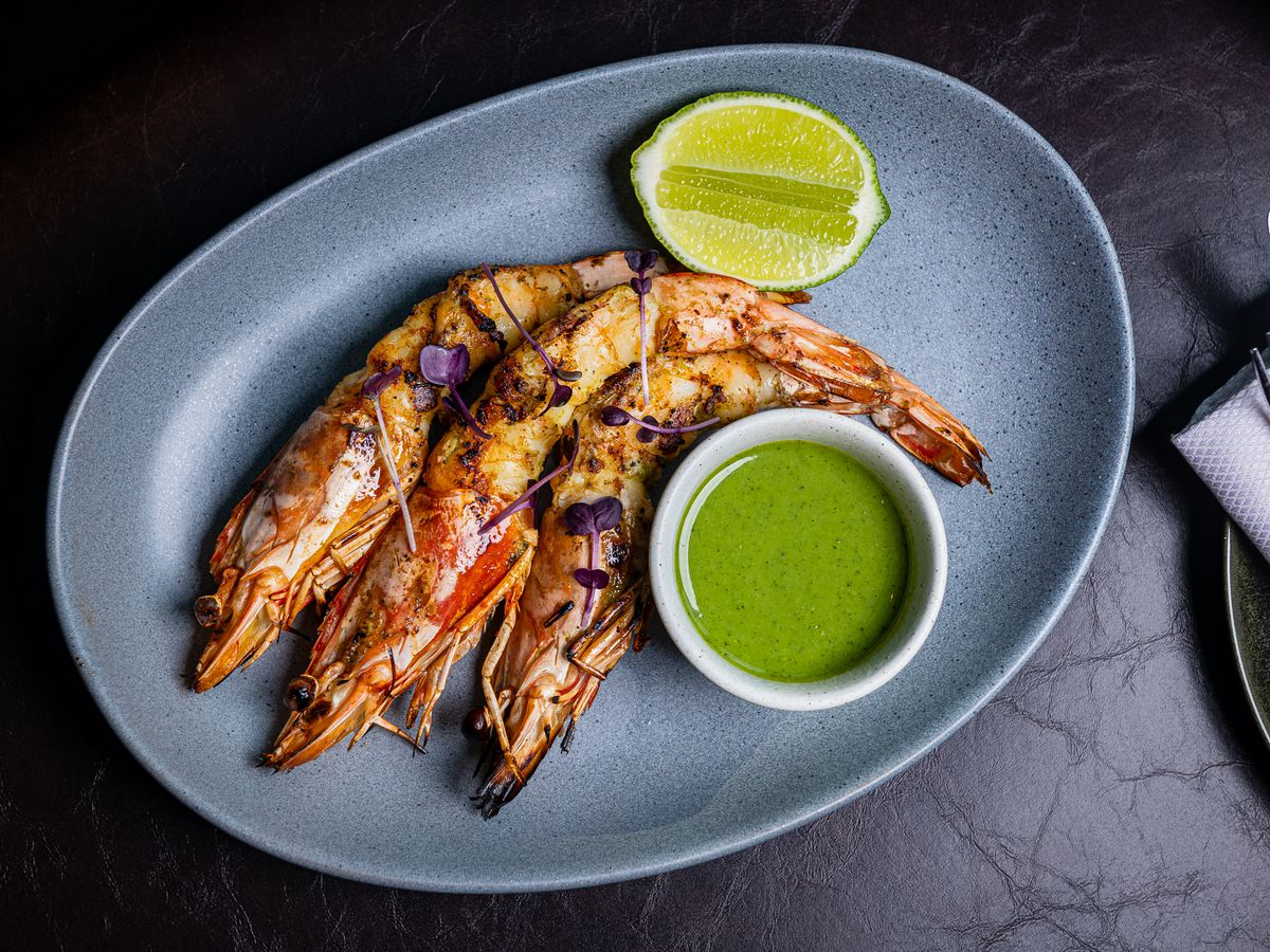 A super spicy condensed milk and chile sauce comes alongside prawns grilled in garlic and Thai basil butter at Moon Rabbit