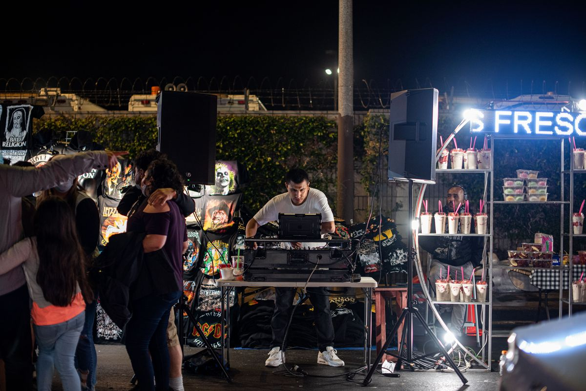 A DJ spins music at a night market, in front of a hedge.