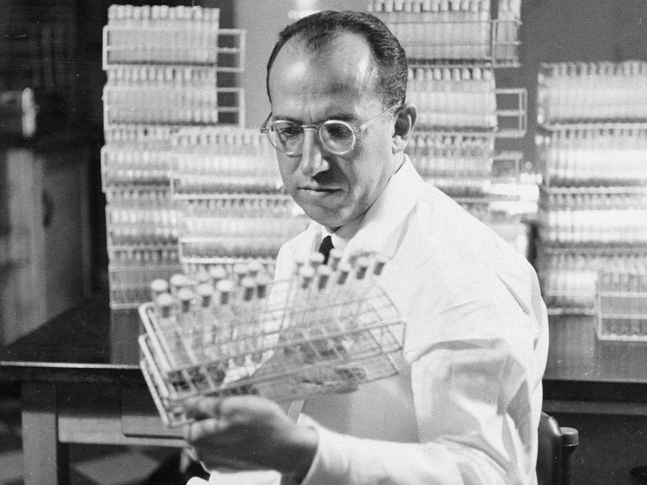 In this Oct. 7, 1954, file photo, Dr. Jonas Salk, developer of the polio vaccine, holds a rack of test tubes in his lab in Pittsburgh.