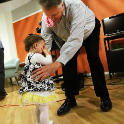 Chad Groesbeck reaches to comfort his granddaughter, Lily Groesbeck, before an interview in Salt Lake City, Monday, March 16, 2015. The 18-month-old survived 14 hours trapped in a car upside down in the Spanish Fork River.