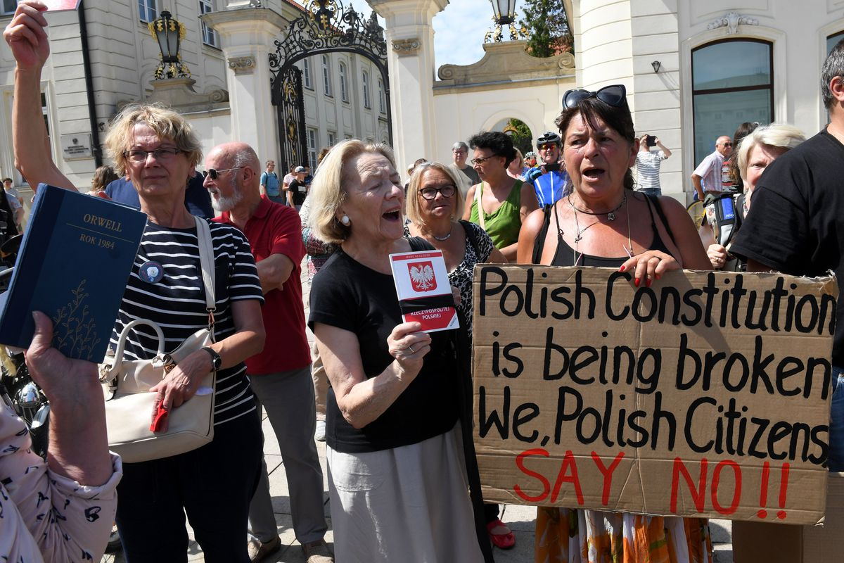 """One demonstrator holds up a sign reading """"Polish constitution is being broken. We Polish citizens say no!"""""""