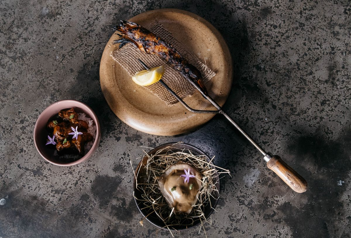 A stick holds a grilled salmon and lemon wedge; a bowl holds an oyster on top of straw at Indigo