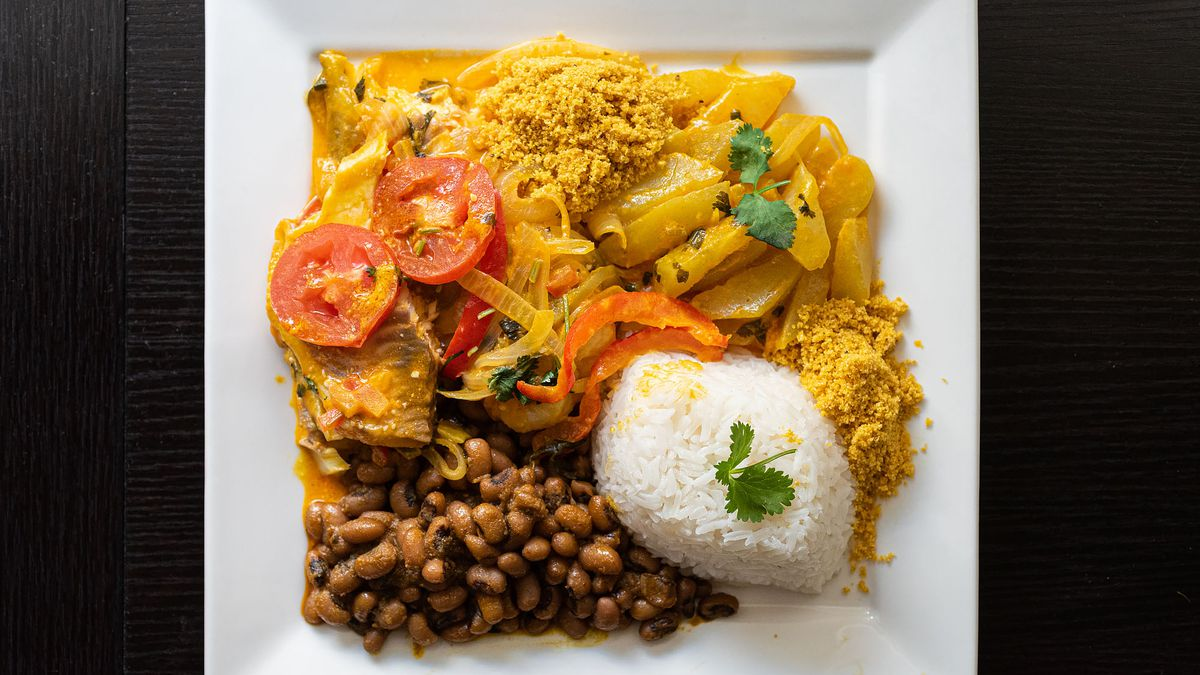 Plate of Brazilian food on a white square plate.
