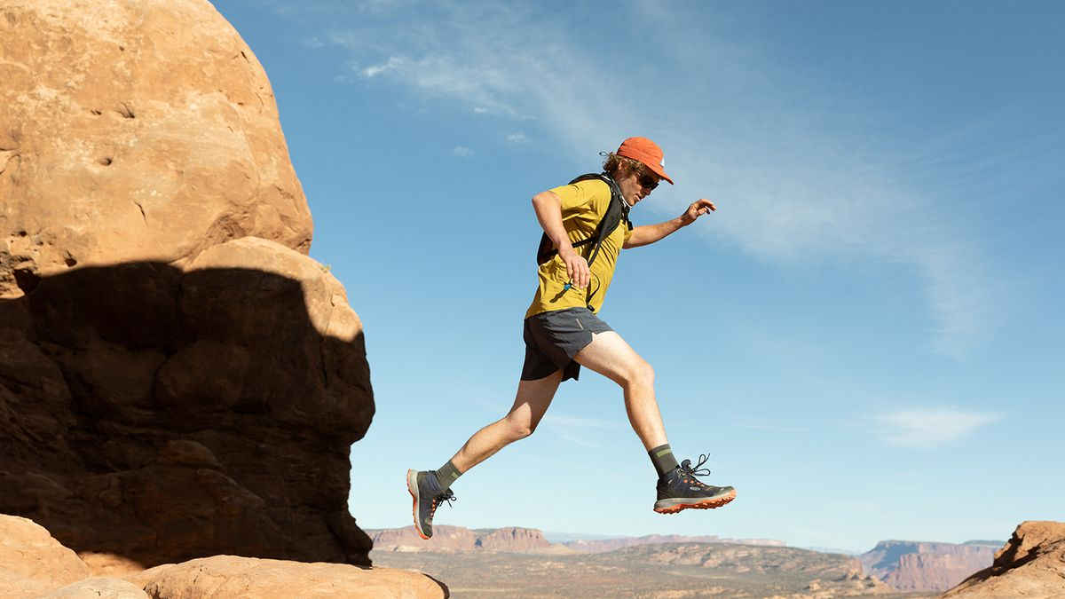 Man enjoying nature and jumping from cliff to cliff on a hike