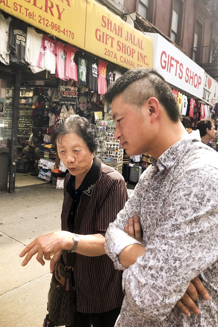 An older Asian woman and a younger Asian man walk and talk together on a street in Chinatown. Behind them are shops selling t-shirts and gifts.