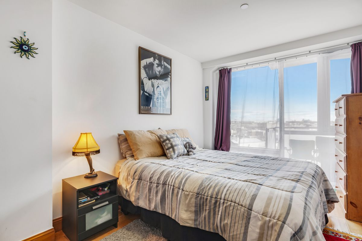 A bedroom with a small bed, hardwood floors, wooden cabinets, and a large glass door that faces a terrace.