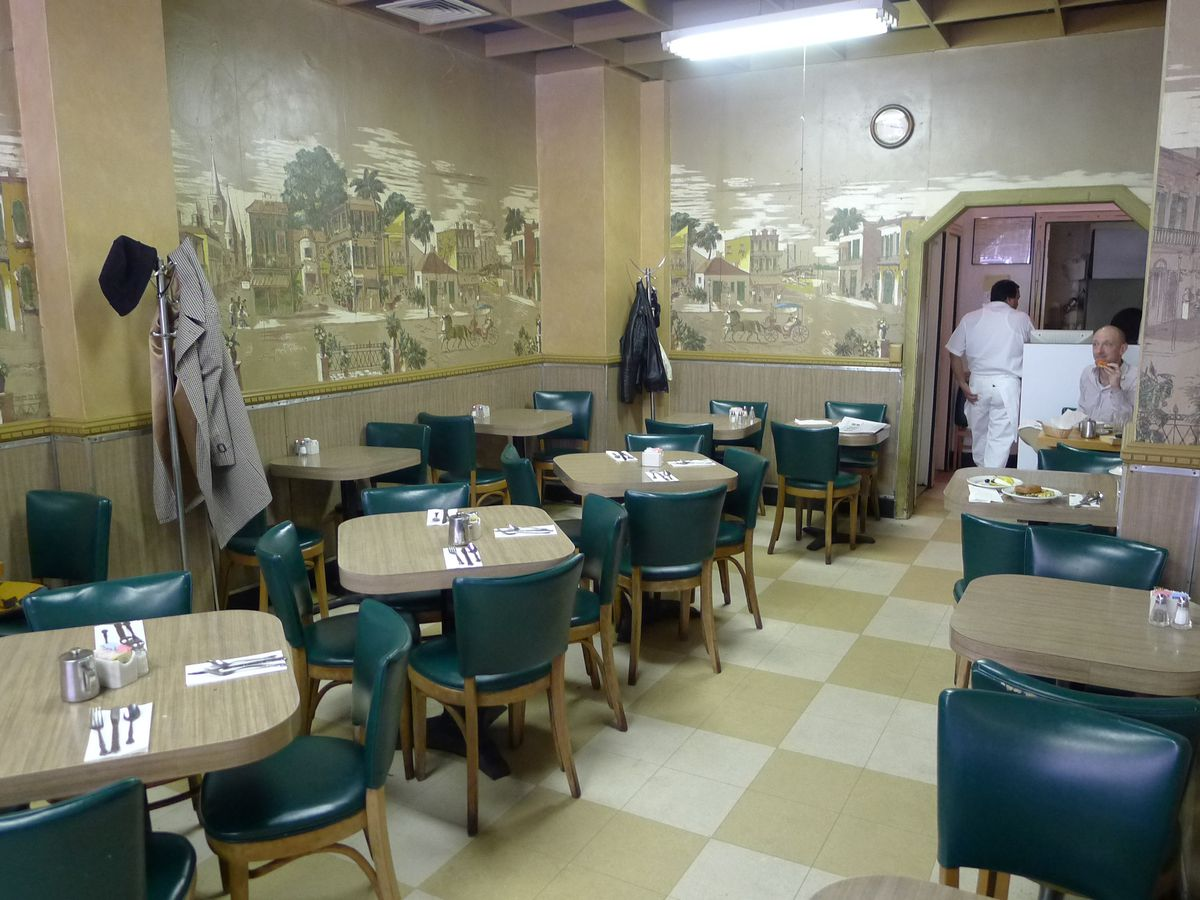 A small, empty restaurant with historical wallpaper