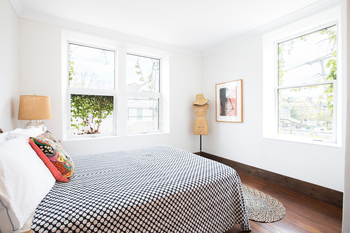A bedroom with oversized windows, wooden floors, and a black and white coverlet.