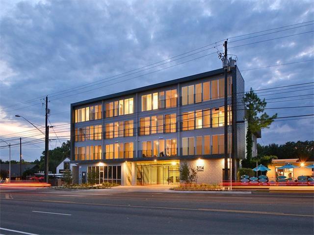 Exterior of contemporary, four-story condo building at dusk