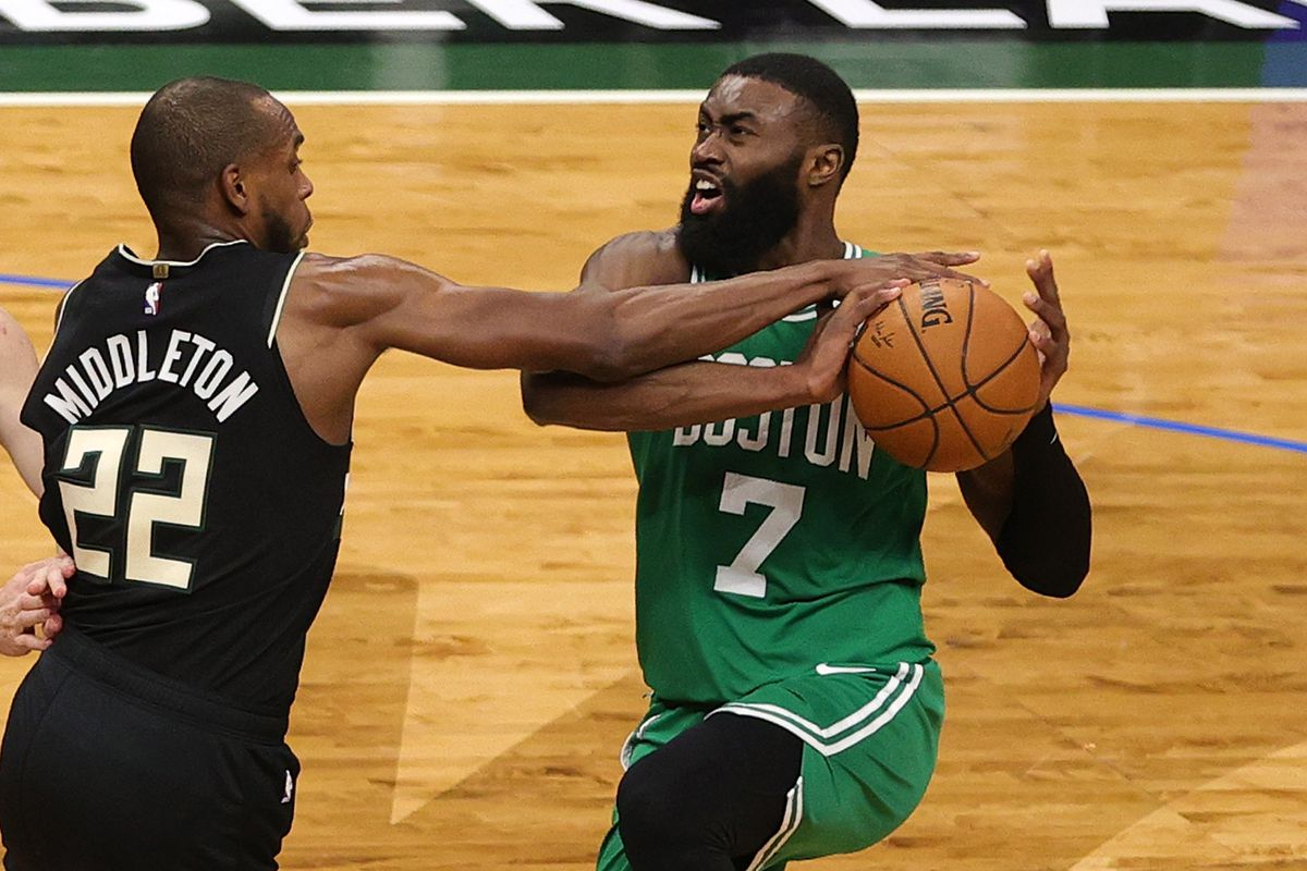 Khris Middleton of the Milwaukee Bucks knocks the ball away from Jaylen Brown of the Boston Celtics during the second half of a game at Fiserv Forum on March 26, 2021 in Milwaukee, Wisconsin.