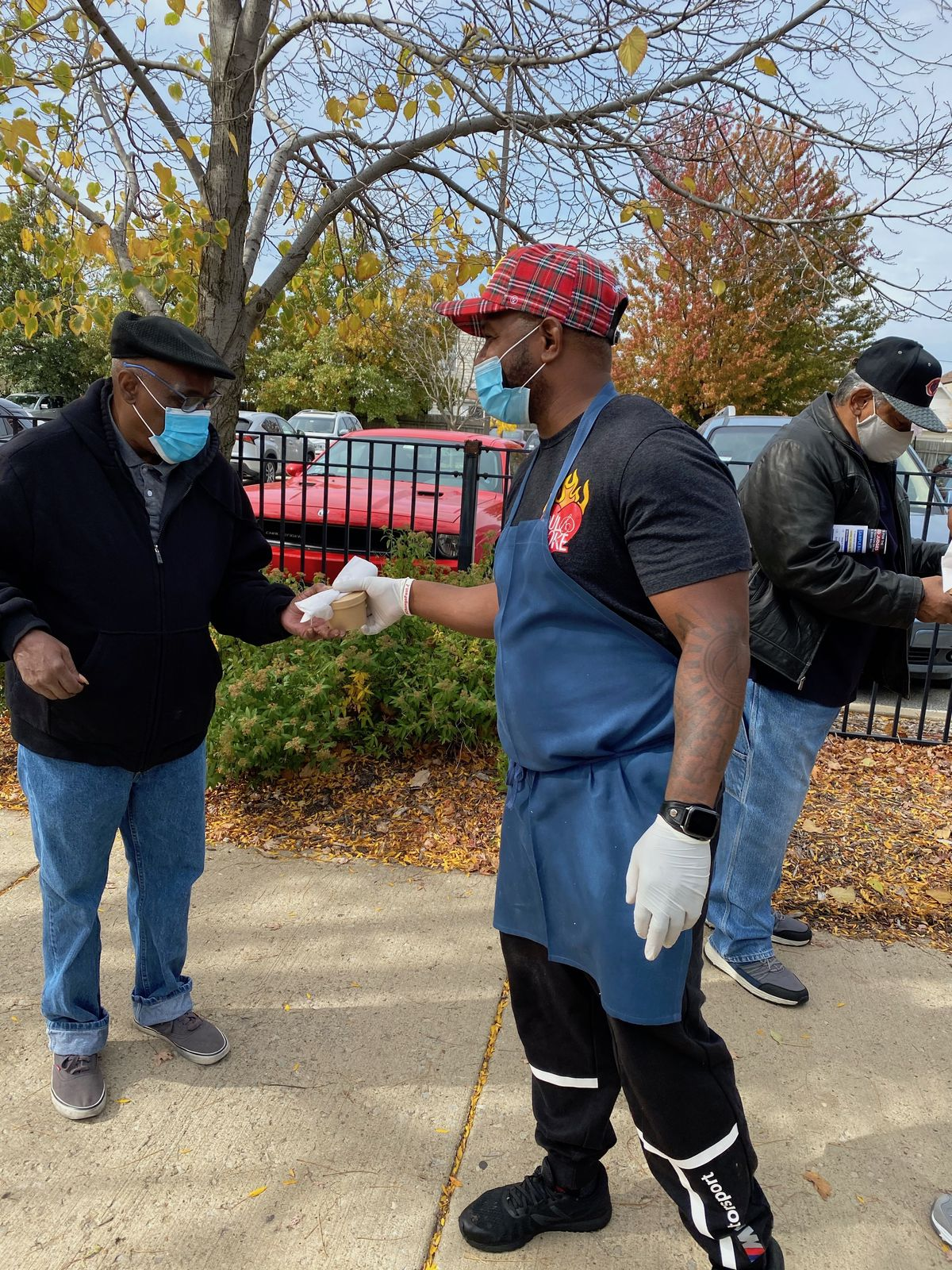 A chef hands a package of food to a man standing on a sidewalk.
