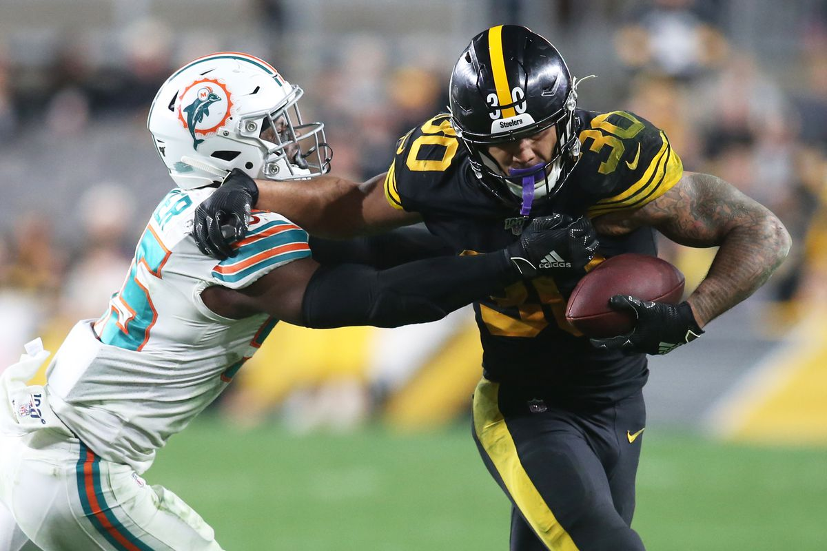 Pittsburgh Steelers running back James Conner runs the ball against Miami Dolphins outside linebacker Jerome Baker during the fourth quarter at Heinz Field. Pittsburgh won 27-14.