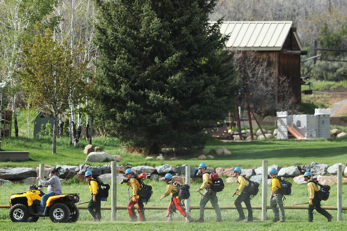 A man on a four wheeler passes hand crews as they begin their hike to fight a wildfire burning in Dutch Hollow area of Midway on Tuesday, May 12, 2020.Multiple agencies responded to the fire.