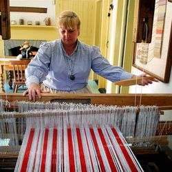 Robin Bromley creates red-and-white dishtowel fabric on an antique loom inside the white-clapboard Jewkes home at This Is the Place Heritage Park. The modest residence was built in Fountain Green, Sanpete County, in the 1860s, and relocated here in the 1980.