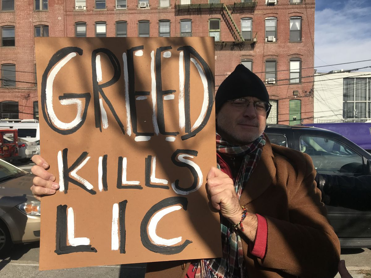 "A protester holds a sign at the anti-Amazon HQ2 protest in Long Island City, Queens that reads ""Greed kills LIC."""