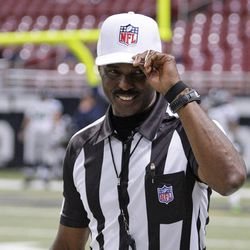 Referee Mike Carey tips his cap to the fans as he walks onto the field before an NFL football game  between the St. Louis Rams and Seattle Seahawks Sunday, Sept. 30, 2012, in St. Louis.