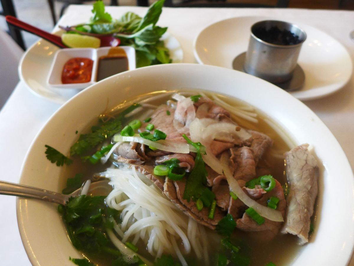 A bowl of pho front and center, with a spoonful of rice noodles raised up, and a plate of basil and cilantro in the background.